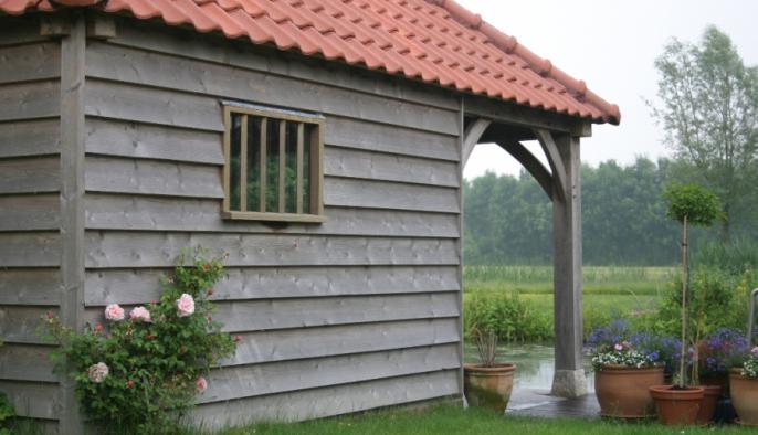 eiken bijgebouw met houten poolhouse en potdekselgevel bij natuur zwemvijver
